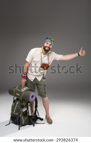 Full length view of male tourist with backpack hitchhiking on gray background - stock photo