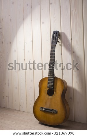 Full length view of one acoustic string light brown color wooden musical instrument of guitar with beautiful shape and fretboard indoor in studio on white wood backdrop, vertical picture - stock photo