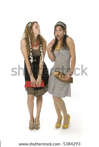 Full length view of two teenage girls in fancy clothes with animated facial expressions.