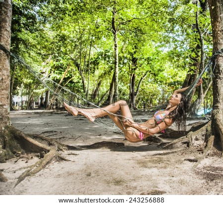 Full length Woman is resting with closed eyes in hammock under palms between trees trunk Brunette girl with long hair tanned skin sunbathing relax and enjoy sun shine Empty space for inscription - stock photo