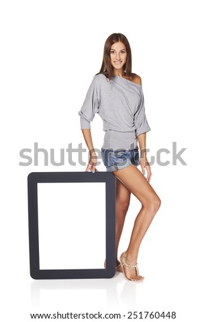 Full length woman showing blank empty screen with copy space. Happy caucasian girl standing with tablet frame over white background - stock photo