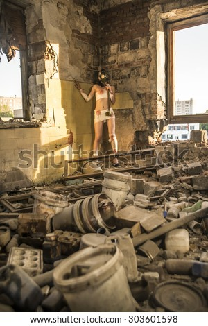 Full length Woman with gas mask in a grunge background Post apocalypse girl stand in angle abandoned dirty yellow wall with shadow from sun light Toxic trash in dusk room Window frame lie on floor - stock photo