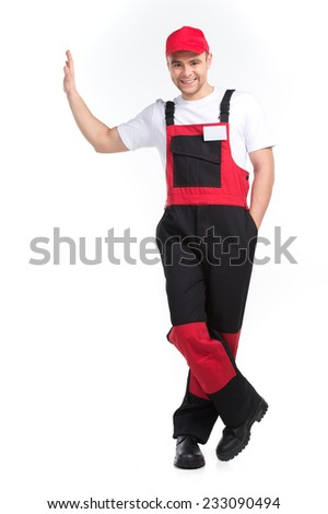 Full length worker in red and black overall. Portrait of mechanic leaning on white background - stock photo