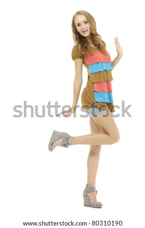 Full length young beautiful female model in colorful dress posing