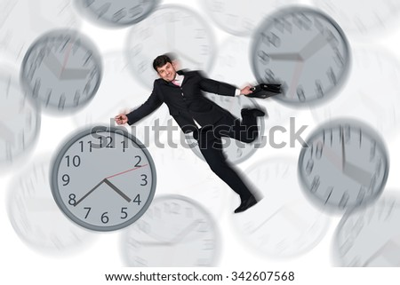 Full length  young businessman running late among clock with a briefcase. Isolated on white background - stock photo