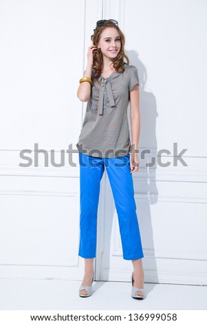 Full length young fashion model posing standing and looking in camera