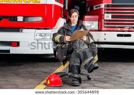 Full length young firewoman writing on clipboard while sitting against trucks at fire station - stock photo