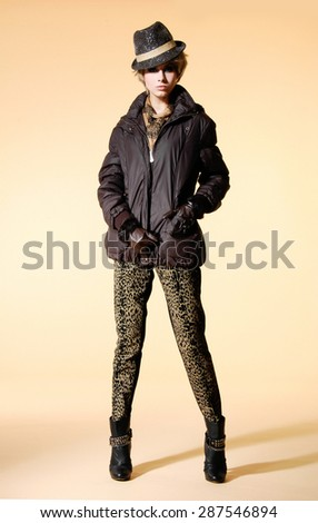 Full length young girl in coat with hat standing on beige background