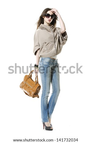 full-length young girl in jeans with sunglasses holding bag posing on white background  - stock photo