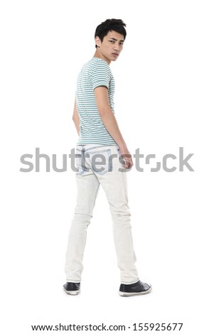 Full length young man in jeans standing back in studio