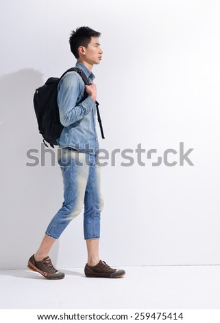 Full length Young man in jeans standing with bag  - stock photo