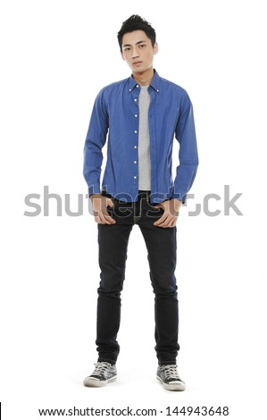 Full length young man in jeans standing with hands in pockets - stock photo