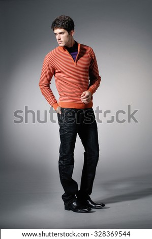 full length young man in sweater dress posing on light background - stock photo