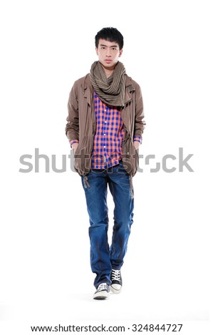 Full length young man standing with hands in pockets walking in studio