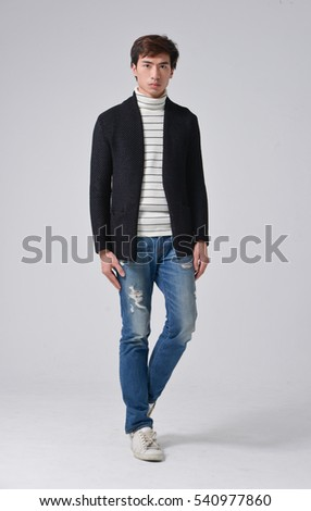 Full length young man walking in jeans walking in studio