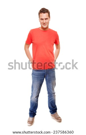 Full length young man wearing red t-shirt jeans casual fashion style with hands in pockets, isolated on white background - stock photo