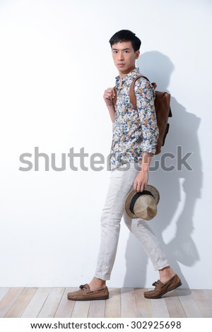 Full length Young man with bag, hat walking on wooden background - stock photo