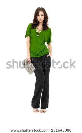 full-length young slim woman holding purse standing in studio  - stock photo