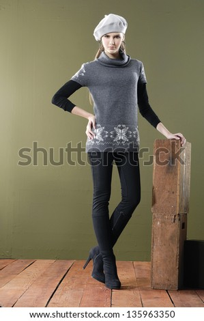 Full length young woman posing with cube on wooden floor - stock photo