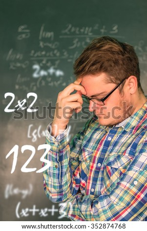Full man in glasses close-up on a background blackboard with mathematical solutions of higher mathematics, he thought about the solution of the problem. The man's face, looking away. figures, numeral - stock photo