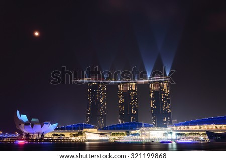 Full moon and lighting show over Singapore landmarks and tourist attraction. Mid-autumn is a big holiday in Asia. People celebrate full moon with moon cake, street lion dancing and flying lantern