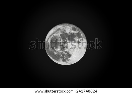 Full moon at a dark night sky with a small glow outside of the moon surface - stock photo