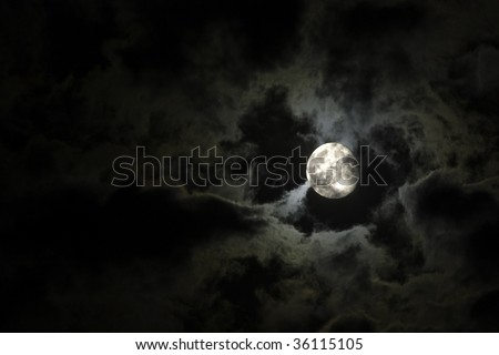 Full moon close-up and eerie white clouds against a black night sky - stock photo