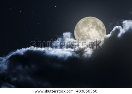 Full moon emerging from behind dark clouds