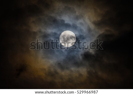 Full moon hidden by clouds, with visible details on it's surface