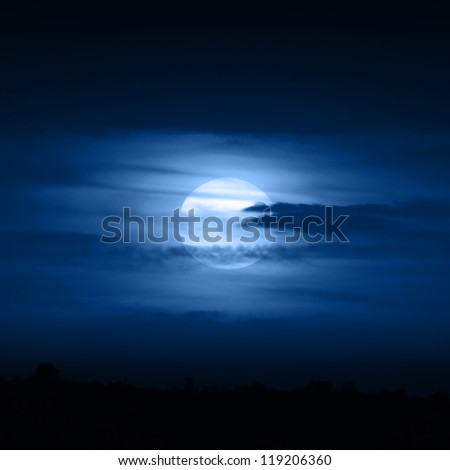 Full moon in blue clouds at night - stock photo