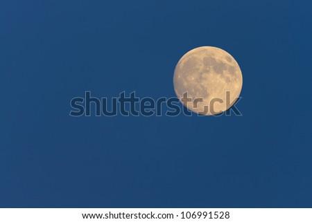 Full moon in dusk sky - stock photo