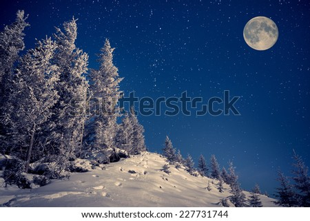 Full moon in night sky in the winter mountains - stock photo