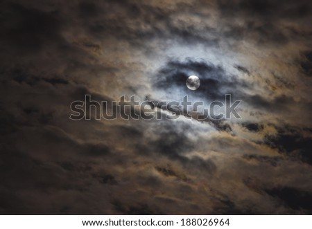 Full moon in the clouds. lunar eclipse  - stock photo