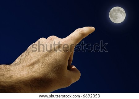 Full Moon. Man's Hand pointing the moon
