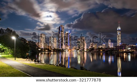 Full Moon Night View of The Iconic Gold Coast City Tourism Skyline Reflecting In The Canal From A Park With Street Lights And Dramatic Clouds, Surfers Paradise, Queensland, Australia - stock photo