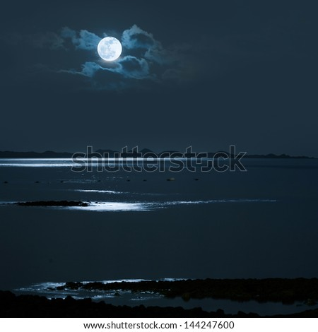 Full Moon over calm sea with a distanc shore - stock photo