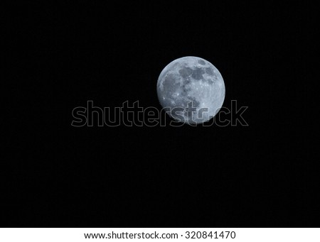 Full moon over dark black sky at night