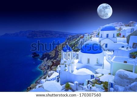 Full moon over Oia town on Santorini island, Greece - stock photo