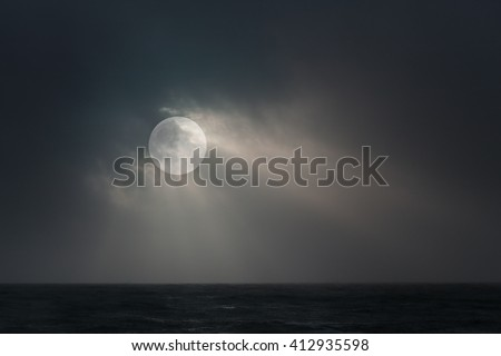 Full moon over sea in an overcast night with moonbeams