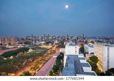 Full Moon Over Singapore Housing Estate by MRT Train Station at Blue Hour - stock photo