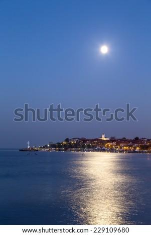 Full moon over the coastal city - stock photo