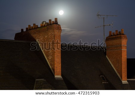 Full moon over the rooftop with chimney at night in Blois, France.