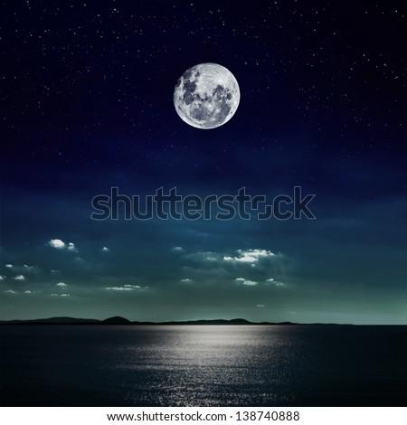 Full moon reflected on the beach - stock photo