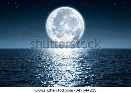 Full moon rising over empty ocean at night with copy space - stock photo