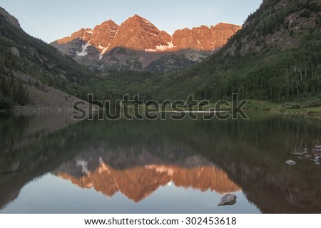 Full moon setting as the sunrise lights the Maroon Bells in Colorado's Rocky Mountains, reflected in Maroon Lake, near Aspen.  - stock photo