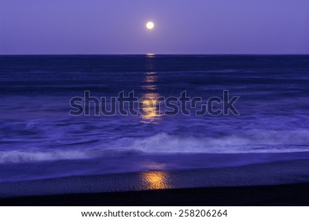 Full Moon setting on Moonstone Beach, along the Big Sur Highway, on the California Central Coast, near Cambria CA. - stock photo