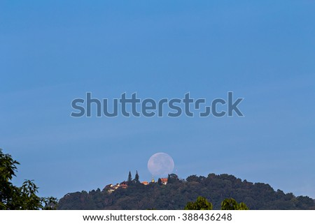 Full moon setting over Buddhist temple on mountain, focus at temple - stock photo