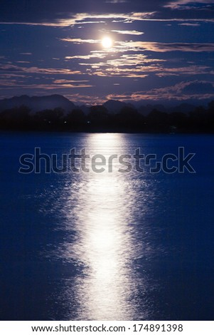Full moon shining down on the river. A calm river at night. - stock photo
