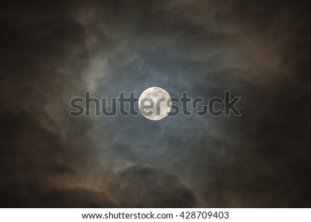 Full moon shining glowing light through the darkness of cloudy.