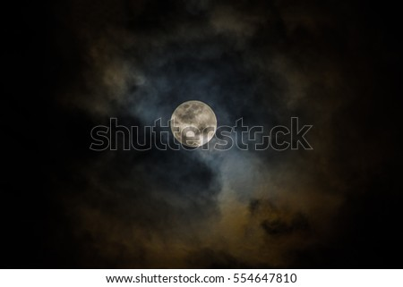Full moon shining through clouds